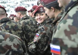 A female member of the NATO KFOR Joint Enterprise for Kosovo force speaks with another member during a farewell ceremony in Vrhnika's military barracks