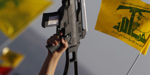 Child holds up plastic toy rifle and waves Hezbollah flag during rally to mark Quds Day in southern Lebanese village of Maroun el-Ras