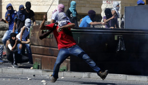 Palestinian uses a sling to hurl a stone towards Israeli police during clashes in Shuafat