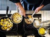 An aerial shot of a chef cooking with several pans on the hob in his restaurant kitchen.