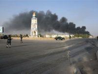 Terlihat polisi Afghan berada di sekitar lokasi ledakan bom mobil, sementara kepulan asap ledakan tampak menghitam. Sumber: AFP