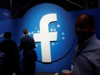 FILE PHOTO: Attendees walk past a Facebook logo during Facebook Inc's F8 developers conference in San Jose, California, U.S., April 30, 2019.  REUTERS/Stephen Lam